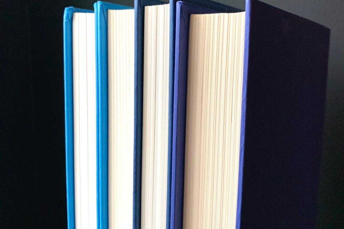 Four books in shades of blue against a black background.