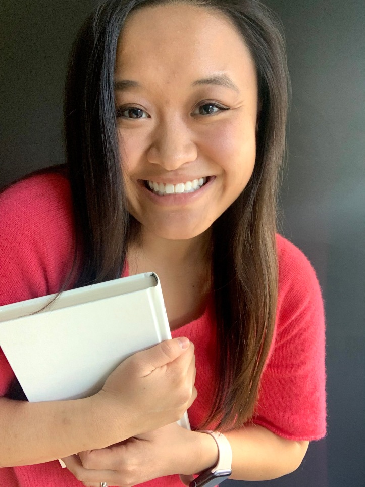 A photo of myself, wearing a red-pink shirt and holding a white hardcover book.