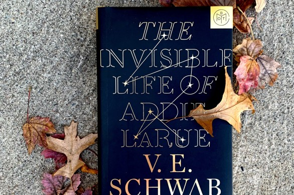 A Book of the Month copy of The Invisible Life of Addie LaRue by V.E. Schwab. The book sits on concrete and is surrounded by fall leaves.