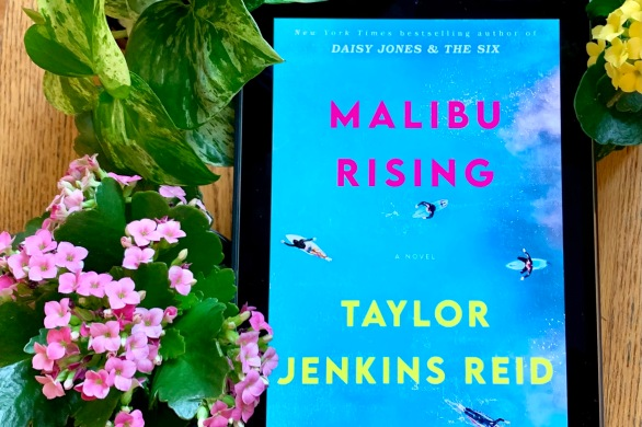 A photo of Malibu Rising on my iPad, surrounded by green leaves and yellow and pink flowers.