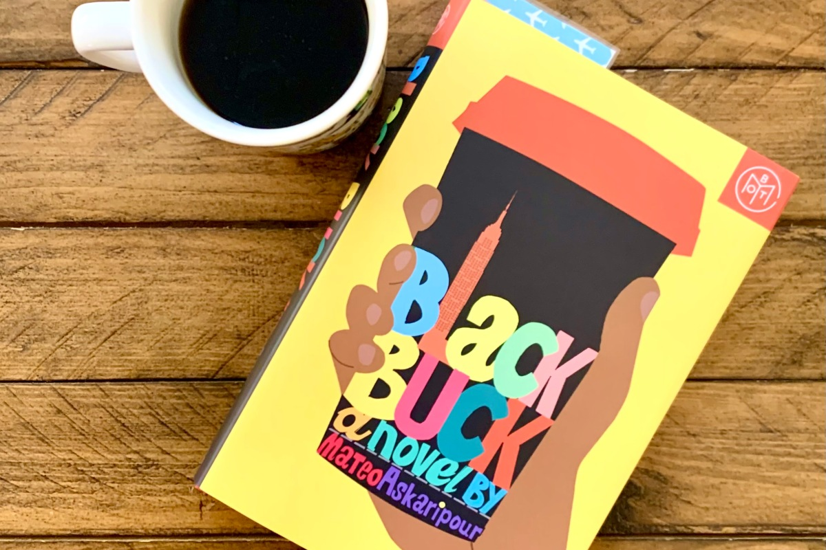 A cup of black coffee next to a Book of the Month copy of Black Buck by Mateo Askaripour on top of a wooden table.