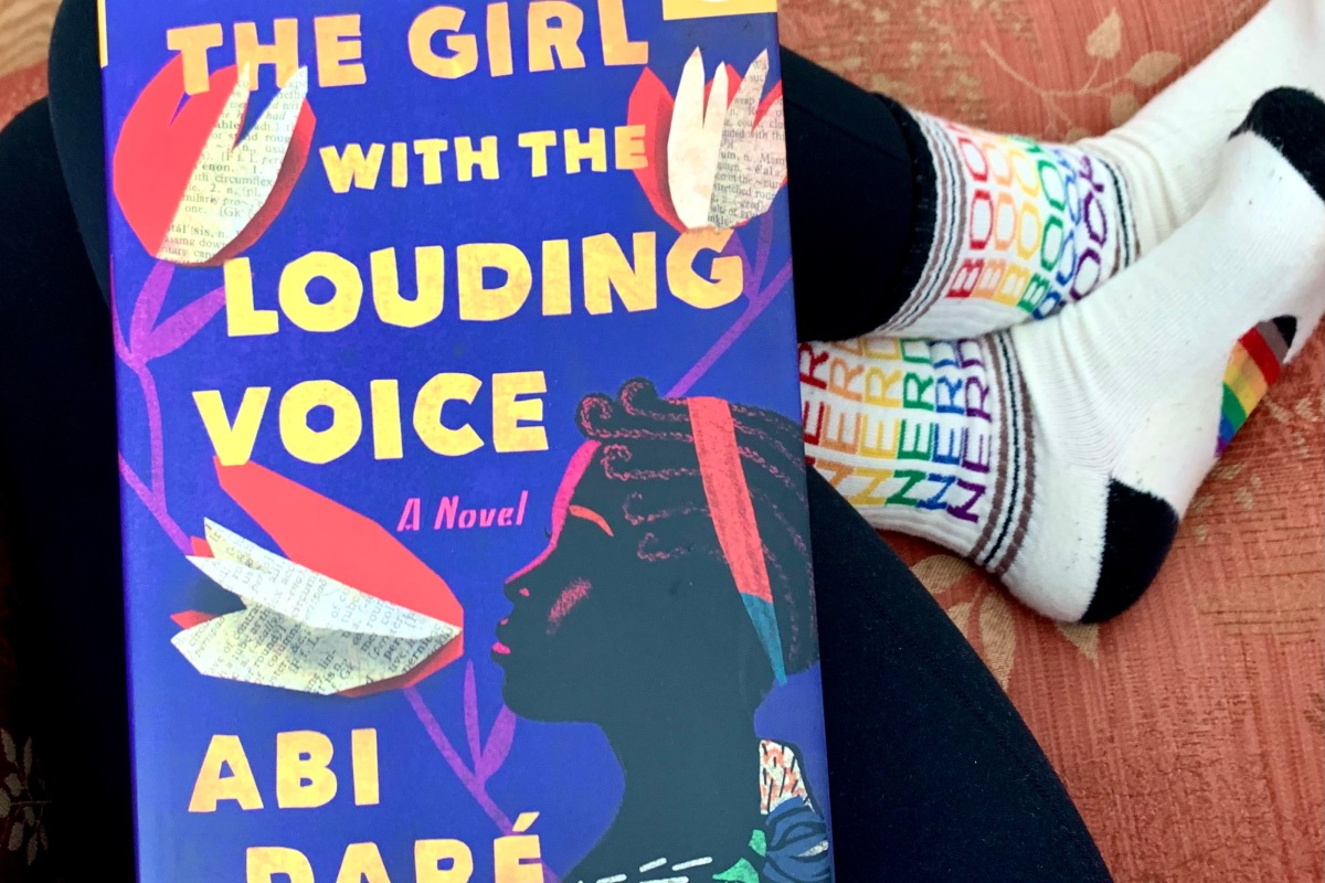 A Book of the Month copy of The Girl With the Louding Voice by Abi Dare sitting on my lap.