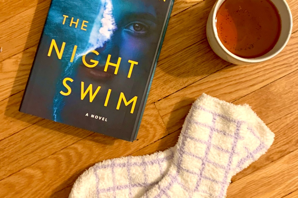 My copy of The Night Swim next to a cup of tea and a pair of fuzzy socks.