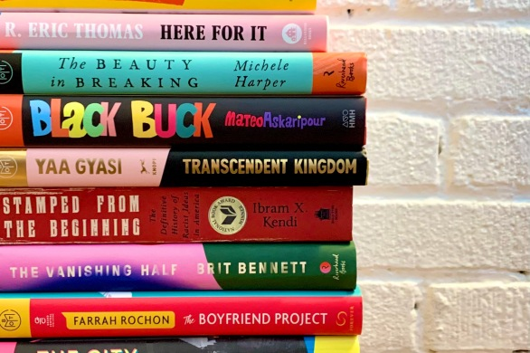 A stack of books, nonfiction and fiction, by Black writers, sitting against a white brick wall.