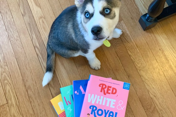 My dog Addie stands next to a stack of my favorite romances.