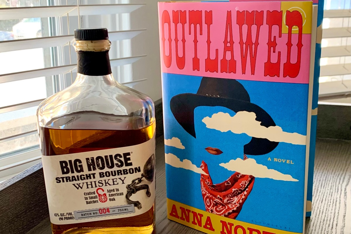 A photo of Outlawed by Anna North next to a bottle of whiskey.