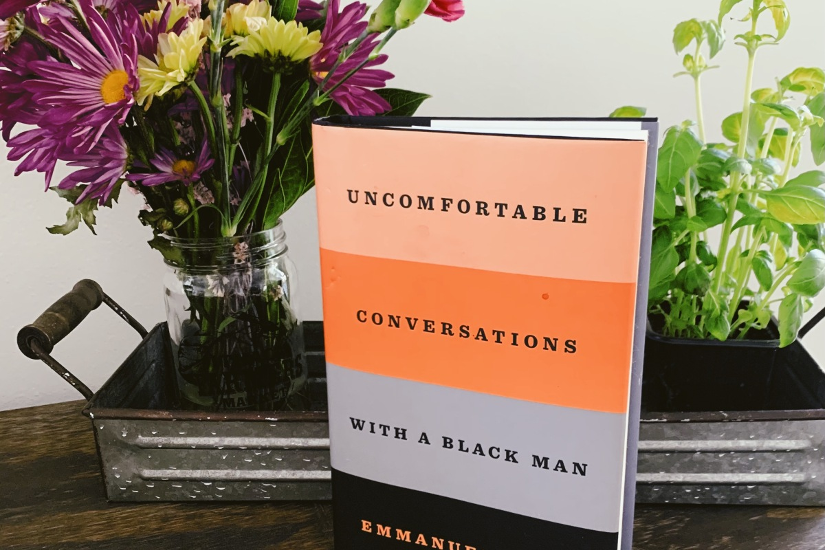 Uncomfortable Conversations with a Black Man sits in front of a vase of purple and pink flowers and a green plant.