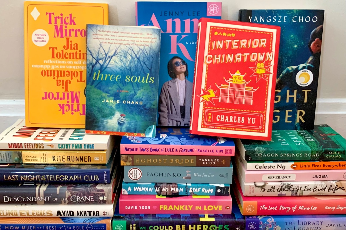 A stack of books by writers of Asian descent. Five are featured prominently, including Trick Mirror, Anna K, Three Souls, Interior Chinatown, and The Night Tiger.