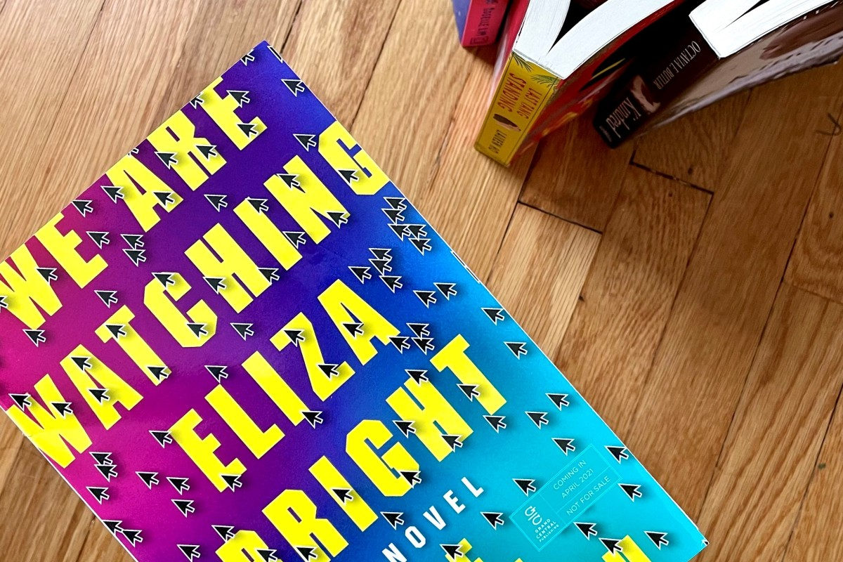 A copy of We Are Watching Eliza Bright by A. E. Osworth. It is purple, pink, and blue with bright yellow print. Books are pointing to it from the top righthand corner.