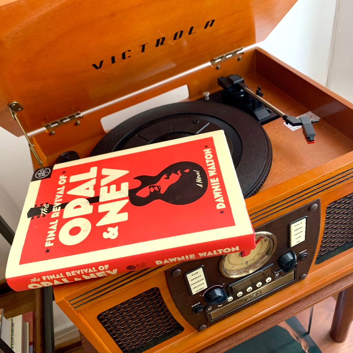 A copy of The Last Revival of Opal and Nev by Dawnie Walton, a red hardcover book with a guitar on the front, set on top of my Victrola record player.
