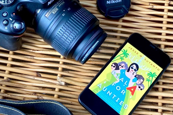 My phone sits on a wicker basket with the cover of Dial A for Aunties by Jesse Q. Sutanto. Next to it is my Nikon DSLR camera and lens cap.